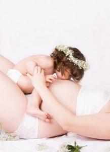 gravida-deitada-com-filha-beijando-a-barriga