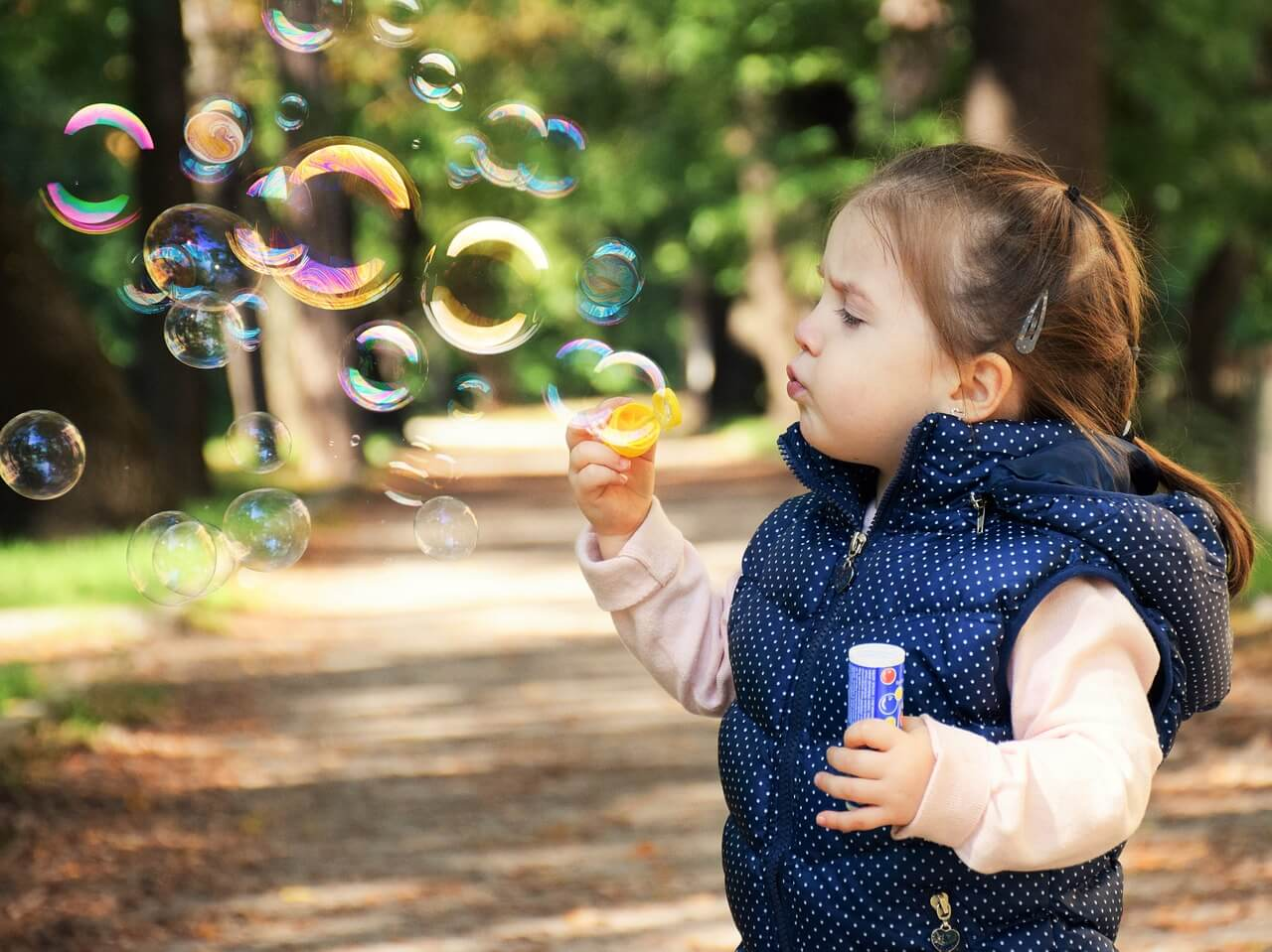 menina fazendo bolhas de sabão