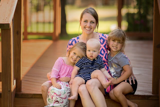 mãe e suas três filhas sorrindo e posando para foto
