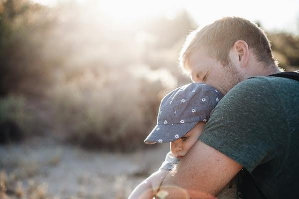 Pai abraçando seu filho no colo