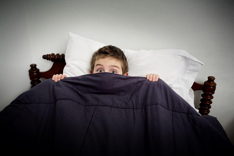 menino deitado na cama, acordando assustado