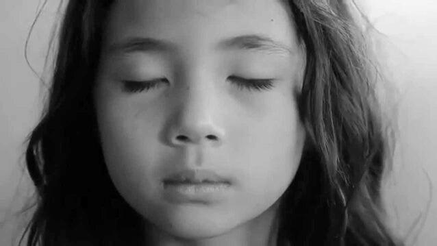 menina de olhos fechados respirando profundamente