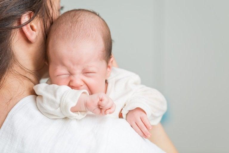 mãe segurando bebê que está sentindo cólicas