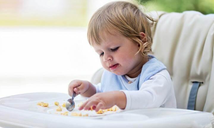 criança comendo por conta própria