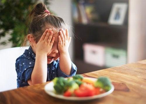 menina com a mão no rosto não querendo comer legumes