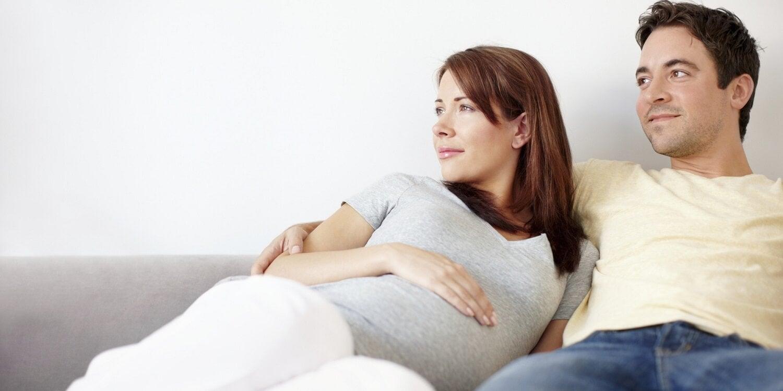 mulher grávida e parceiro juntos olhando para o mesmo lugar