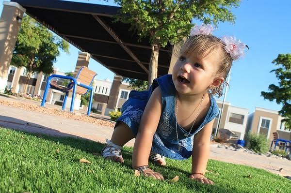 bebê de quatro no chão engatinhando; conquista do primeiro ano
