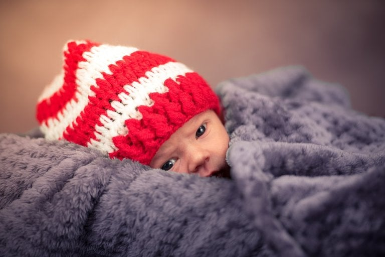 recém-nascido com goro na cabeça e manta de frio