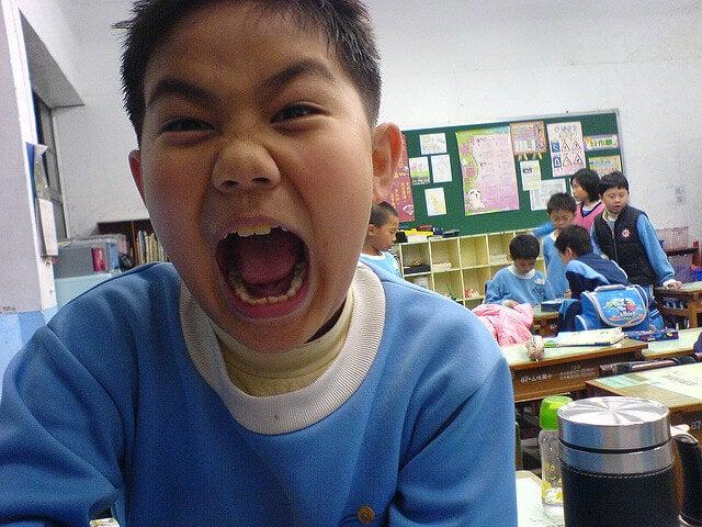 menino gritando irritado na escola