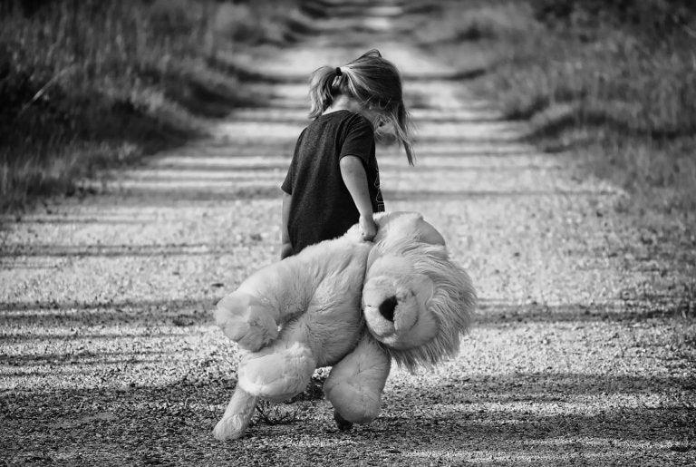 menina andando sozinha em uma estrada carregando um bicho de pelúcia