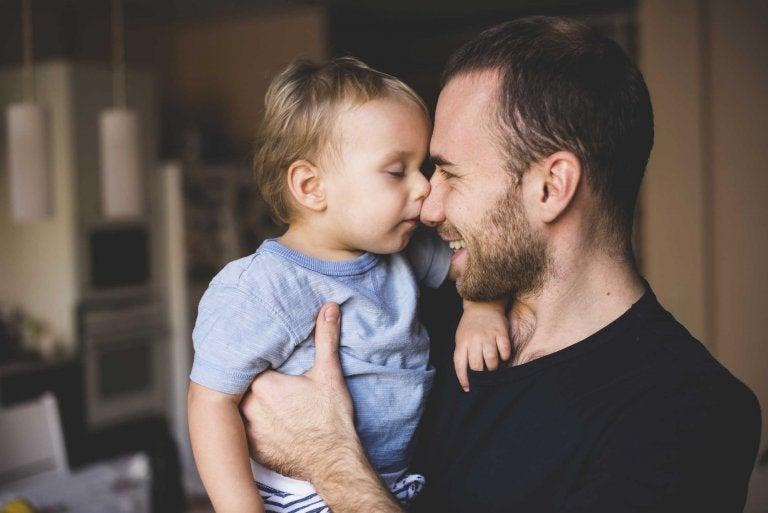 pai sorrindo e segurando seu filho no colo