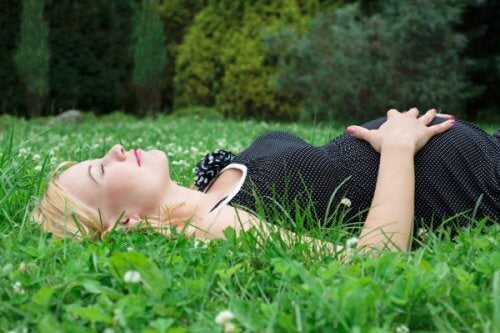 mãe deitada na grama contando os chutes do bebê