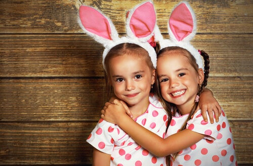 duas irmãs gêmeas vestidas de coelhinho se abraçando