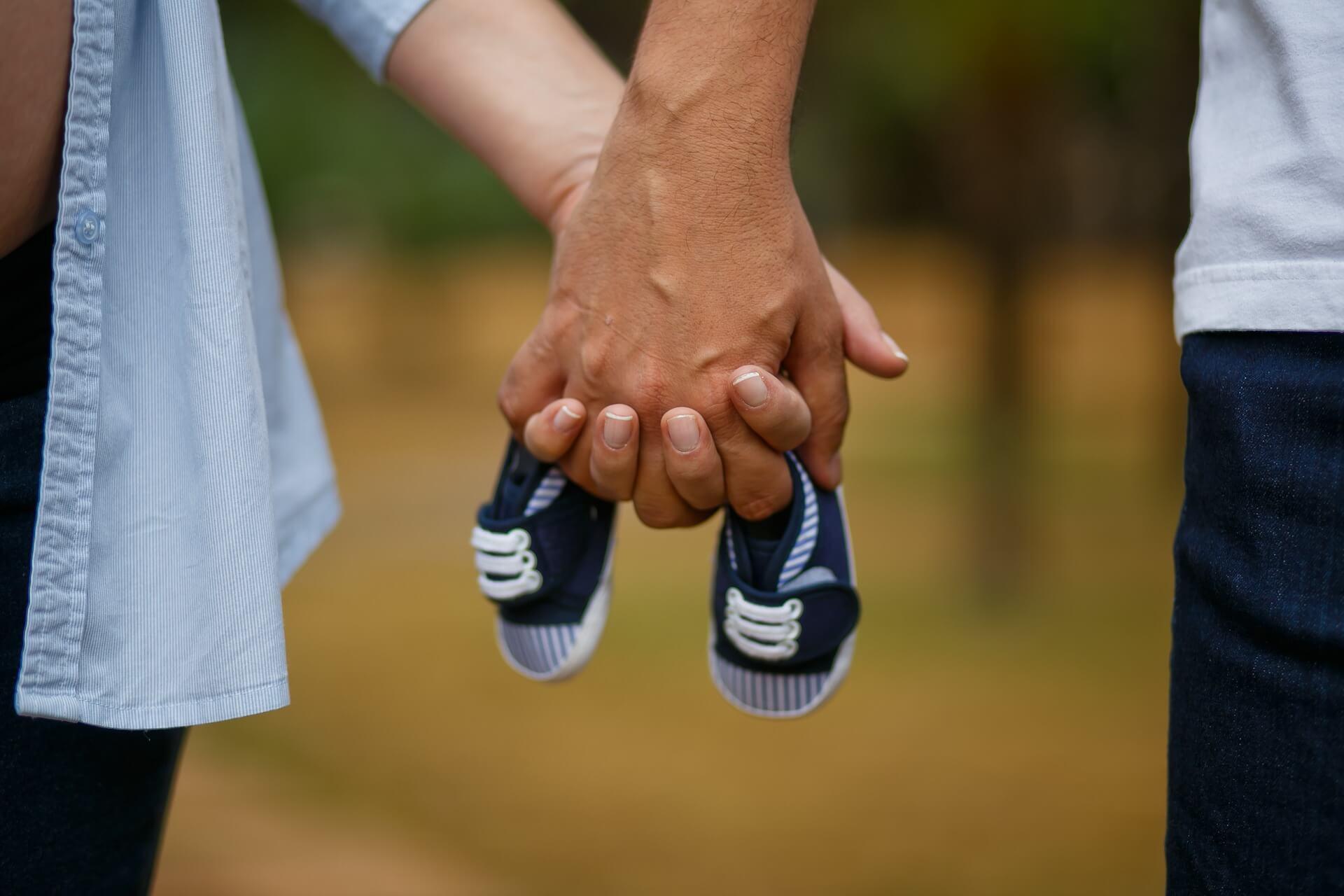 casal de mãos dadas segurando os sapatinhos do futuro bebê