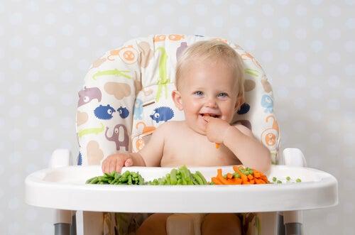 bebê sentado em uma cadeira de alimentação comendo legumes