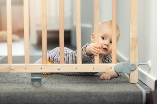 bebê segurando as grades de proteção da escada