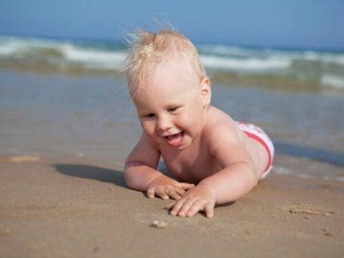 bebê engatinhando sobre a areia da praia