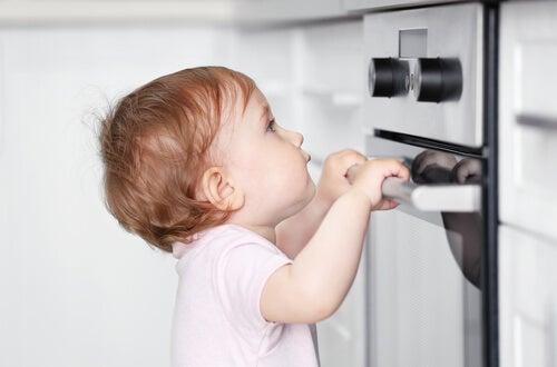 menino segurando a porta do fogão