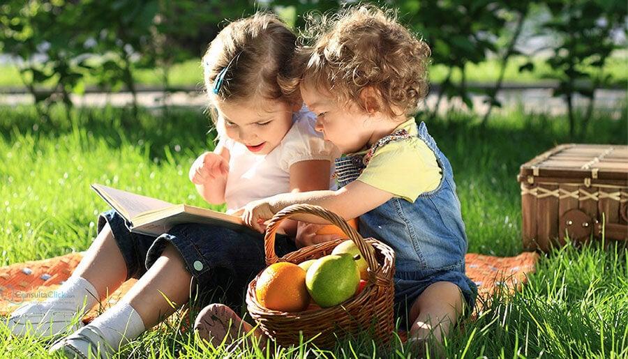 duas crianças sentadas na grama lendo um livro