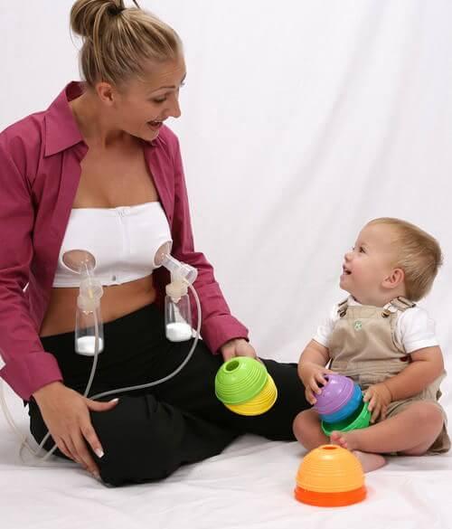 mãe usando a bomba tira-leite nos seios ao lado do seu bebê