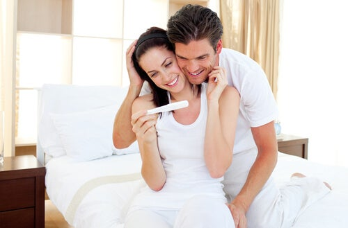 Casal olhando juntos o resultado do teste de gravidez