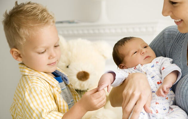 irmão mais velho segurando a mão do novo irmãozinho
