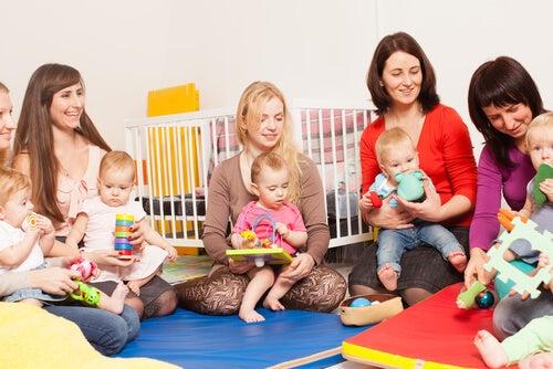 mãe sentadas no chão da creche com seus filhos no colo