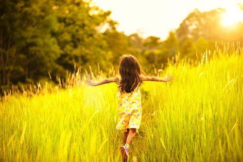 menina correndo no meio da grama alta