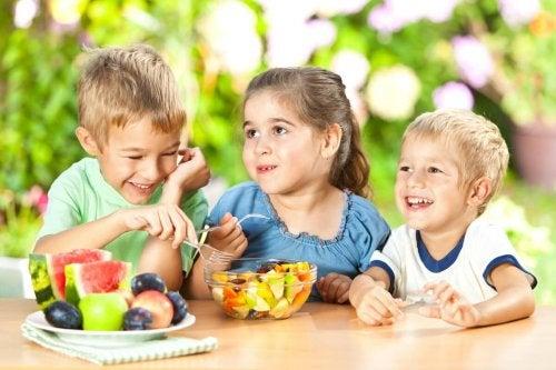 Três crianças juntas comendo um salada de frutas