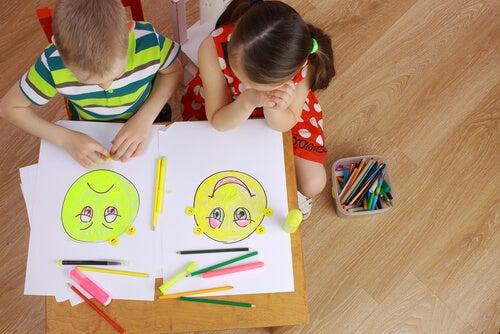 menino desenhando uma carinha triste e menina desenhando uma carinha feliz