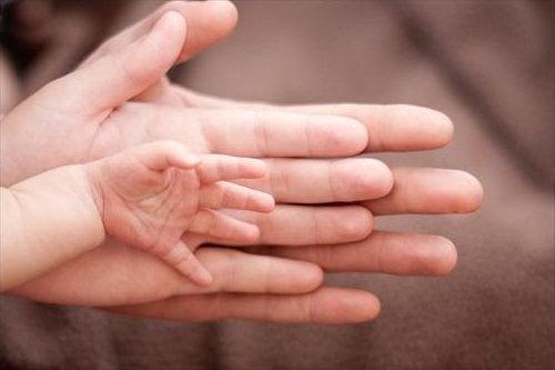 três mãos juntas, do pai, da mãe e do bebê