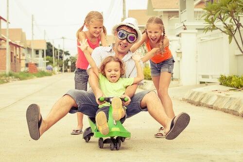 pai brincando de carrinho com seus filhos