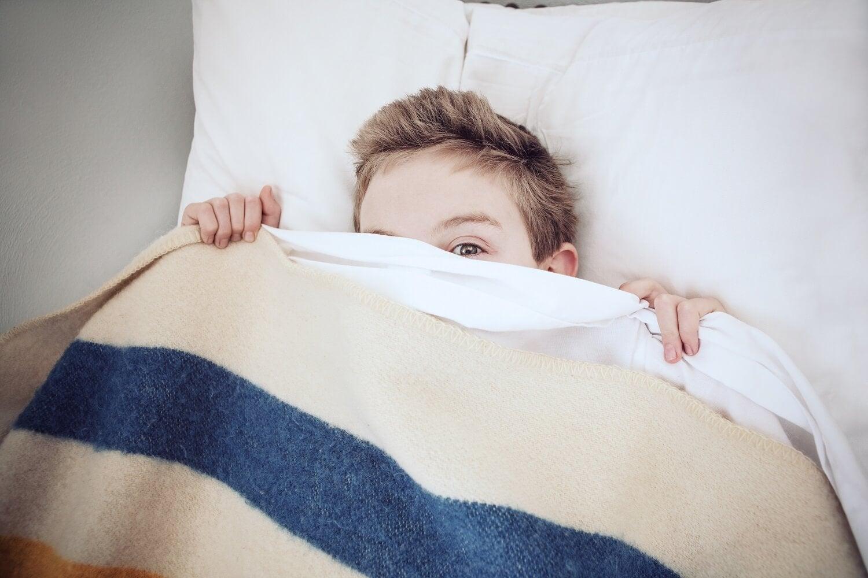 menino na cama se escondendo sob os lençóis com medo