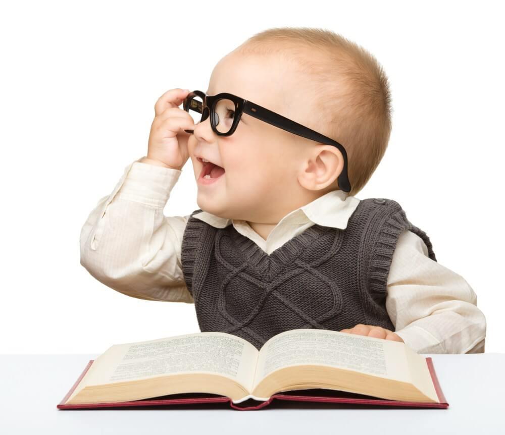 menino usando óculos e com um livro na mão