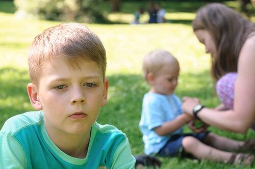 mãe dando atenção ao filho mais novo, irmão mais velho com ciúmes
