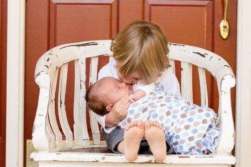 menino com irmão mais novo no colo, beijando-o