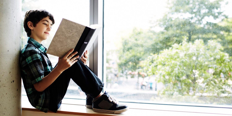 menino lendo um livro na janela do quarto