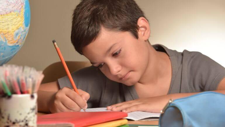 menino fazendo as lições de casa
