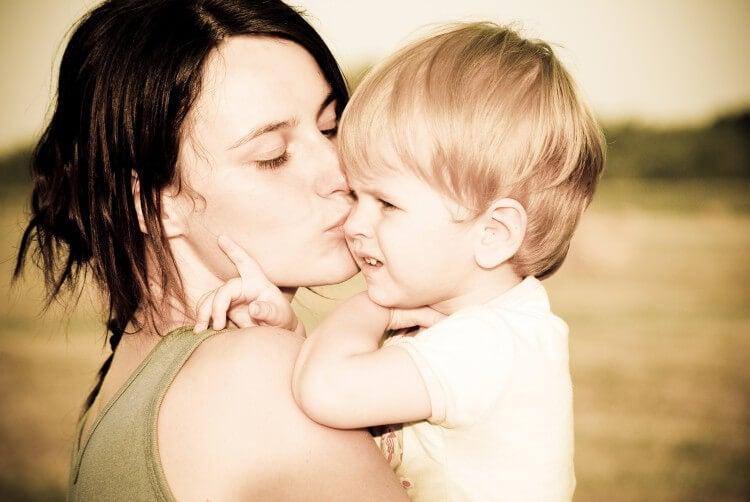 mãe com o seu filho no colo beijando-o