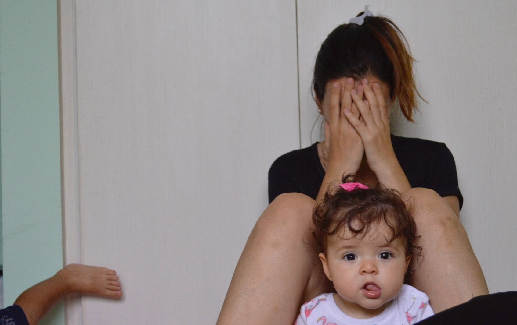 mãe sofredora chorando perto de seus filhos