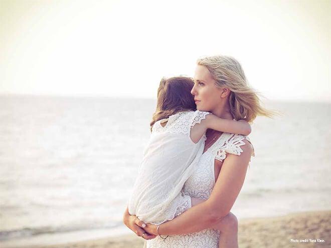 Mãe com a filha na praia desfrutando um momento de pausa