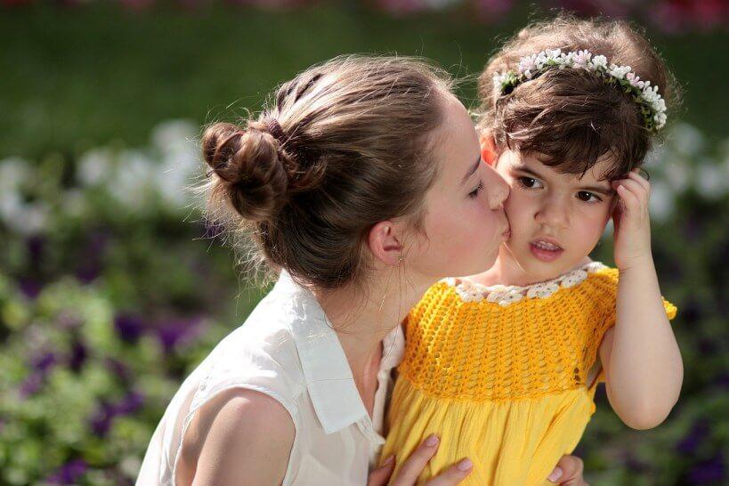 criança sendo beijada por uma mulher