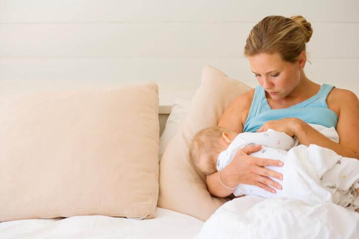 mãe deitada sobre a cama amamentando o seu bebê