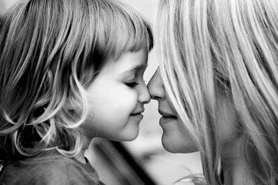 mãe e filha sorrindo e fazendo carinho