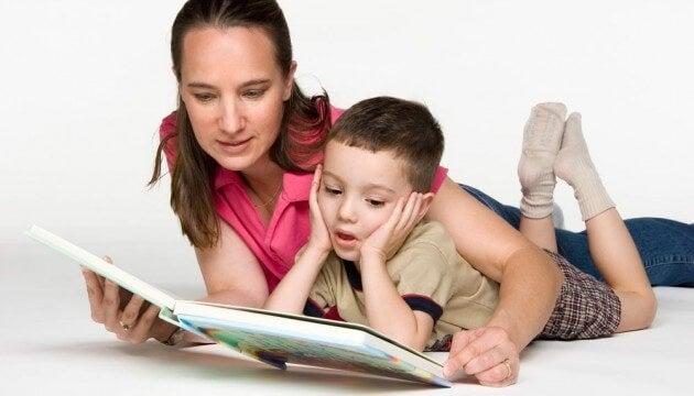 mãe deitada no chão lendo com o seu filho