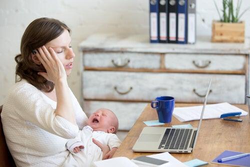 mãe cansada com o seu bebê chorando nos braços