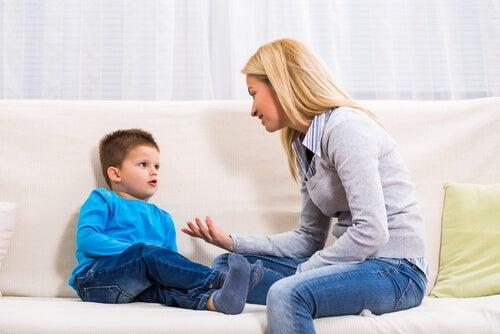 mãe sentada no sofá disciplinando seu filho