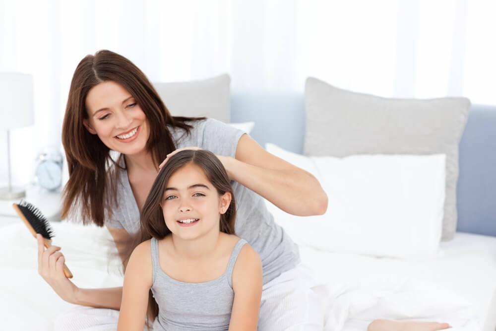 Mãe penteando o cabelo da filha