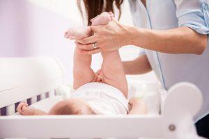 mãe limpando o bebê sobre o trocador