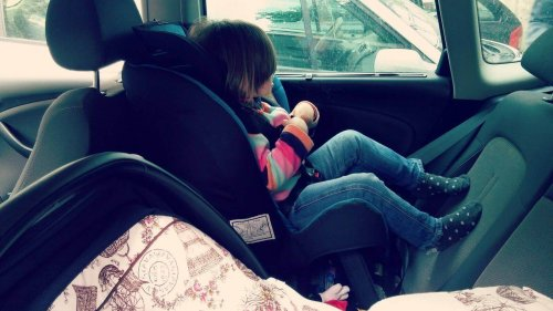 criança sentada em cadeirinha de carro com assento voltado para trás
